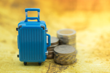 Travel Concept. Close up of blue miniature baggage with stack of coins on world map.