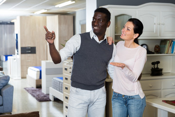 Adult woman with her husband are looking on modern furniture for their house