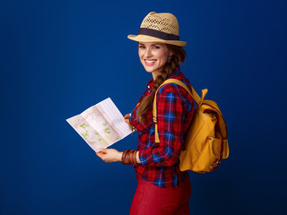 smiling fit traveller woman against blue background with map