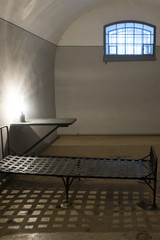 The old prison cell in which the bed, table, lamp, window with a lattice