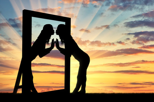 Woman is kissing her reflection in the mirror