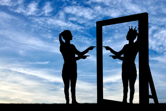 A silhouette of a narcissistic woman raises her self-esteem in front of a mirror