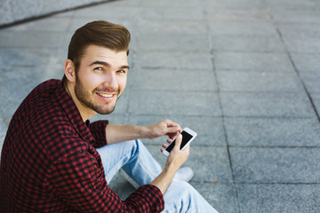 Smiling young man using his phone outdoors