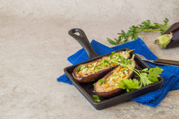 Young fried eggplants with greens on a black cast-iron frying pan on a blue napkin.