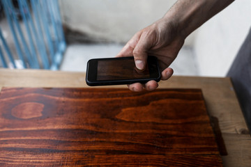 Male hand holding a cell phone and taking a image of a freshly painted wooden plank