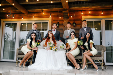 .stylish bride and groom with guests sitting on the terrace of the houses