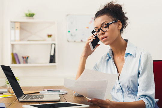 Serious woman consulting by phone at office