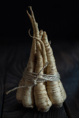 A bunch of parsley root on dark wooden table
