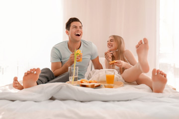 Young lovely couple having breakfast on bed