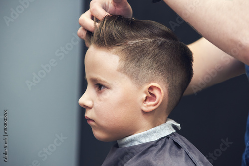 Barber Making Hairstyle To A Caucasian Boy Using Hair Gel Stock