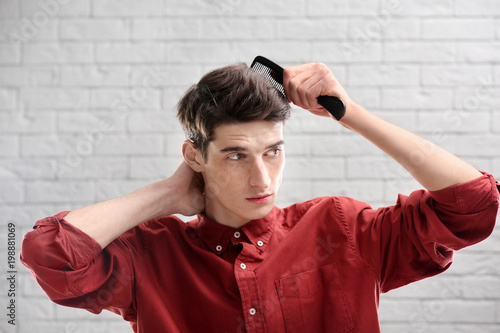 Portrait Of Young Man Combing His Hair On Brick Wall