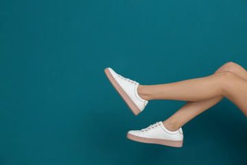 Legs of beautiful woman in stylish shoes on color background Wall mural