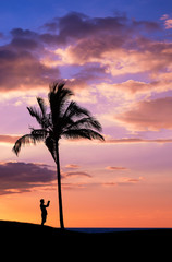 Tropical sunset with silhouettes of a photographer and a palm tree