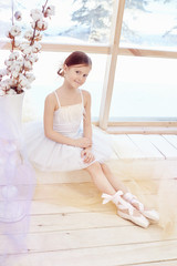 Young ballerina girl is preparing for a ballet performance. Little prima ballet. Girl in a white ball gown and Pointe near the window, beautiful red hair. Young theater actress