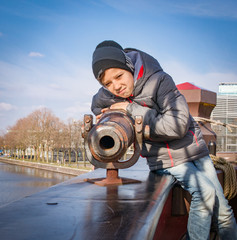 Boy aiming a canon at a target, on an old sailing ship, Amsterdam, Holland. Vintage vessel.