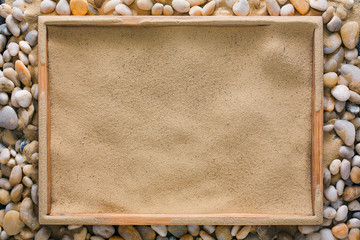 Beach sand in wooden tray on sea pebbles