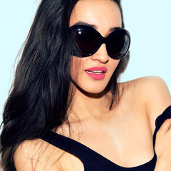 Portrait of a brunette in stylish sunglasses. Summer vibes