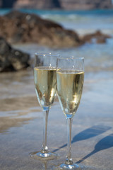 Two glasses of champagne or cava sparkling wine served on the white sandy tropical beach, luxury resort with sea view, romantic vacation