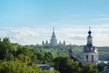 The buildings of Moscow city center with State University silhouette, some classical old church and colorful roofs. Beautiful city view of Moscow lush green nature, outdoor summer evening in Russia.