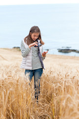 Young girl in wheat field taking picture by smartphone