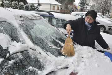 Woman driver cleans the snow from the car