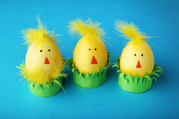 Yellow eggs with funny chicken faces on blue background