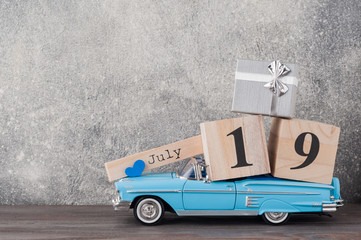 Father's day concept. A toy car with gifts, heart, 19th of July on wooden background. Copy space for Fathers day greeting card.