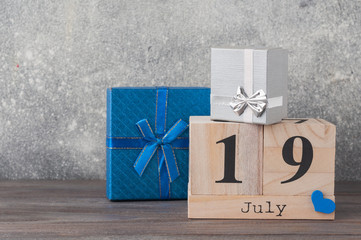 Father's day concept. Gifts (presents), heart, 19th of July on wooden background. Copy space for Fathers day greeting card.