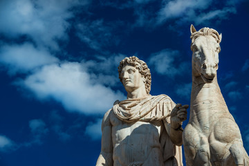 Ancient marble statue of Castor or Pollux with horse, dated back to the 1st century BC, located at the top of monumental balustrade in Capitoline Hill, in Rome (among clouds)