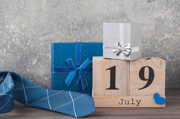 Father's day concept. A tie with gifts, heart, 19th of July on wooden background. Copy space for Fathers day greeting card.