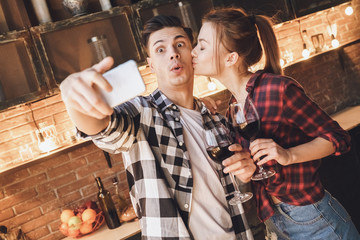 Selfie time. Shoked man looking at camera, woman kiss him