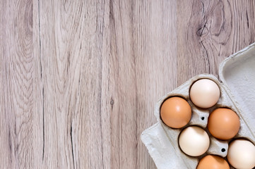 Fresh raw chicken eggs in carton egg box on wooden background. The top view on brown and white eggs. Close-up view. The main ingredient for many dishes. Free space for inscriptions, notes.