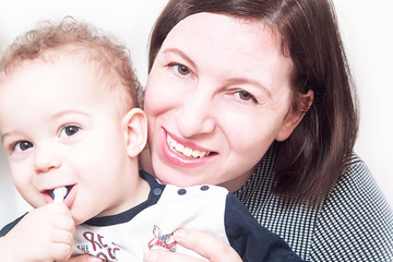Portrait of a happy mother poses in front of camera with her baby