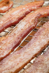 Macro close up on fried bacon strips with grease bubbles, on a wire cooling rack