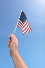 Hand holding American flag on a bright sunny day