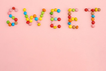 The inscription Sweet of colorful candies on a pink background