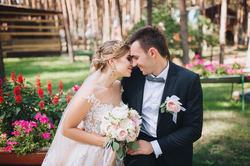 Happy newlyweds gently kiss and smile. Wedding walk in nature.