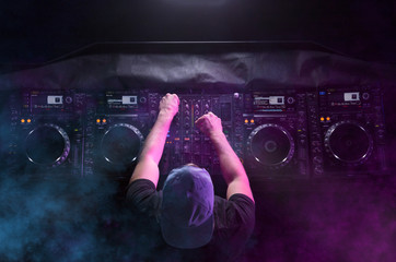 Disc jockey at the turntable. DJ plays on the best, famous CD players at nightclub during party. EDM, party concept.