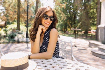 Image of young woman with beautiful hair and charming smile is sitting in summer cafeteria in sunlight. She is wearing pretty summer dress and black sunglasses. Background park. Beautiful portrait.