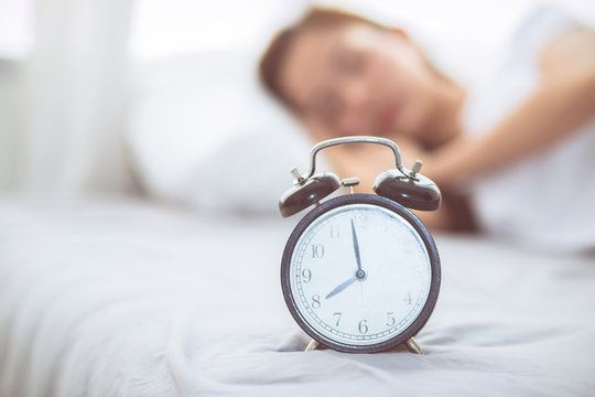 Beautiful asian young woman turn off alarm clock in good morning, wake up for sleep with closeup foreground alarm clock, relax and lifestyle concept.