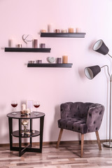 Burning candles on wall shelves and table in room interior