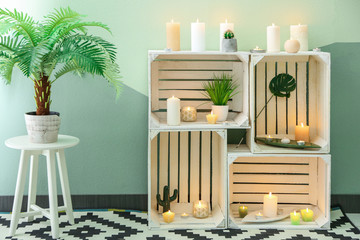Shelf unit with many burning candles indoors