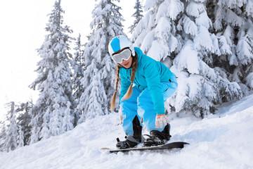 Female snowboarder on ski piste at snowy resort. Winter vacation