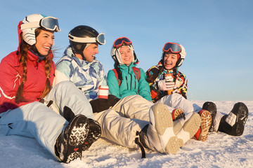 Happy friends sitting on snowy mountain peak at ski resort. Winter vacation