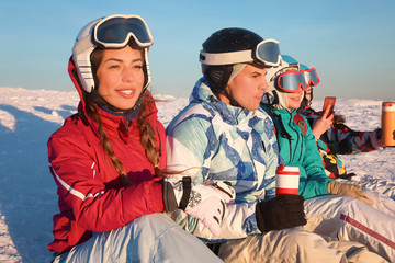 Group of friends enjoying the beauty of sunset at snowy ski resort. Winter vacation