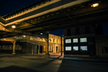 Fotomurales - Dark and eerie Chicago urban city street night scenery with elevated CTA train tracks, vintage industrial warehouses and factories.