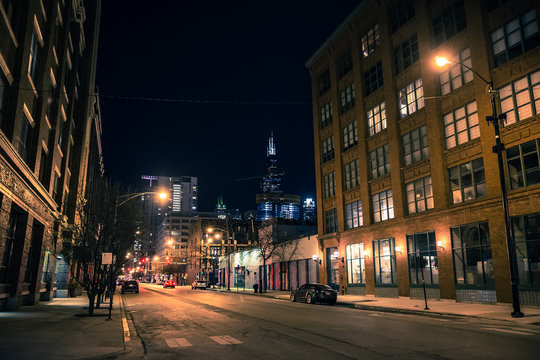 Chicago city street night scene in the West Loop with the skyline and Sears Willis Tower skyscraper in the background