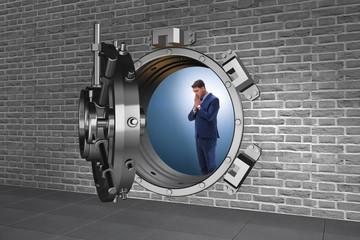 Businessman concerned about theft at banking vault door