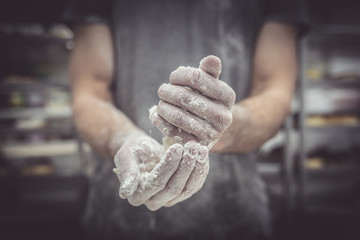 Baker hands with dough and flour on the hands,selective focus