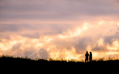 Silhouette scene of a couple enjoy with their drone at sunset on the top of Mt. Eden, Auckland, New Zealand.